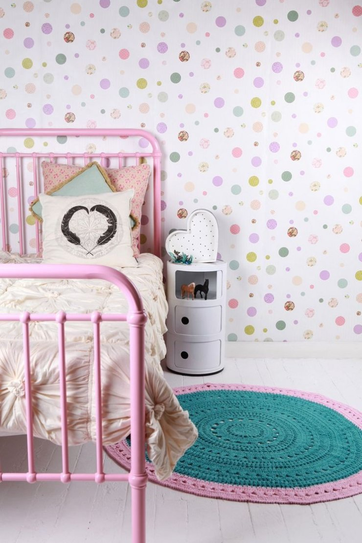 pink iron bed and dotted wall